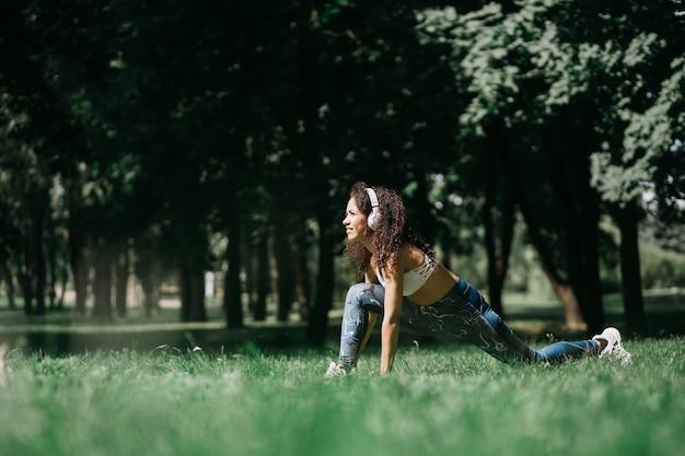 Femme souriante dans les écouteurs faisant des étirements avant de faire du jogging en plein air