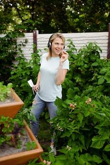 Femme souriante dans les écouteurs travaille avec des fleurs dans le jardin