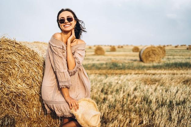 Femme souriante, dans, lunettes soleil, à, épaules nues, sur, a, fond, de, champ blé, et, balles foin