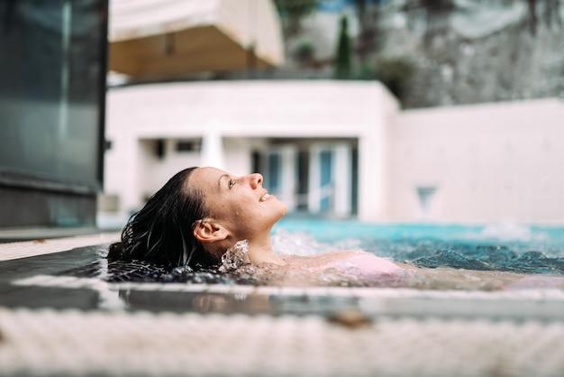 Femme souriante dans la piscine de la station thermale.