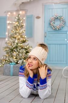 Une femme souriante dans un pull tricoté et un chapeau blanc se trouve sur une terrasse décorée pour les vacances de noël. portrait d'une jolie fille sur une véranda lumineuse en vêtements de noël