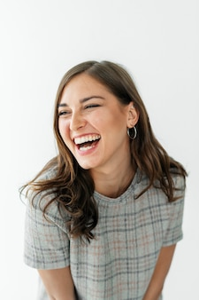 Femme souriante dans une robe à carreaux grise