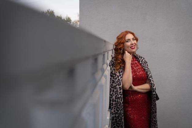 Une femme souriante dans une robe de soirée rouge se dresse sur le balcon