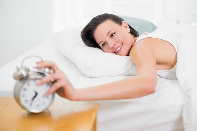 Femme souriante dans son lit, étendant la main au réveil