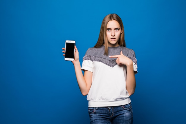 Femme souriante dans des vêtements décontractés à l'aide de smartphone sur fond bleu.