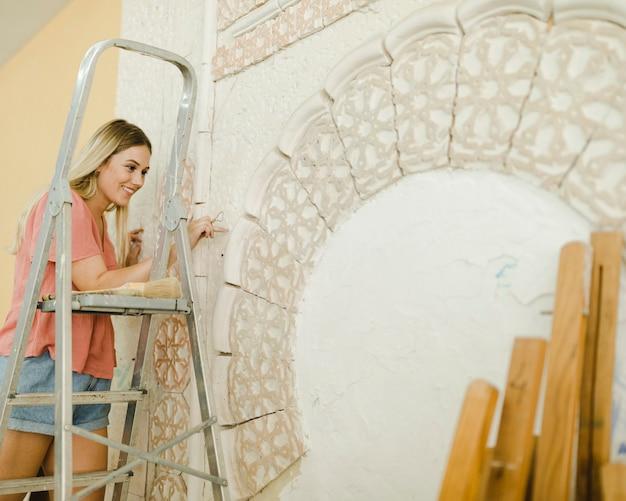 Femme souriante, debout, sur, échelle, découpage, sur, mur
