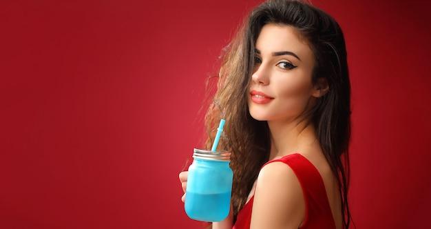 Femme souriante debout avec pot à boire en studio