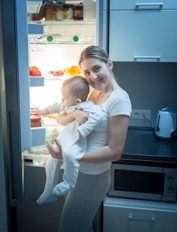 Femme souriante debout avec son bébé dans la cuisine la nuit