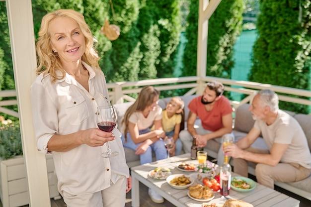 Une femme souriante debout avec un verre de vin dans les mains
