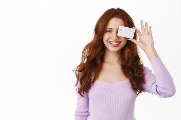 Femme souriante, dents blanches, montrant une carte de crédit bancaire, paiement sans contact, debout sur blanc