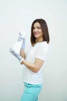 Femme souriante détient un vaporisateur avec un antiseptique ou un détergent comme des pistolets santé ou concept de nettoyage covid sur fond blanc