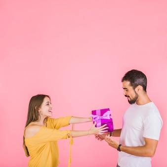 Femme souriante, donner, rose, boîte cadeau, à, elle, petit ami, debout, contre, rose, toile de fond