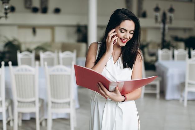Femme Souriante Avec Dossier Parlant Au Téléphone Photo Premium