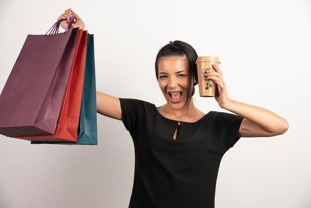 Femme souriante avec du café tenant des sacs à provisions.