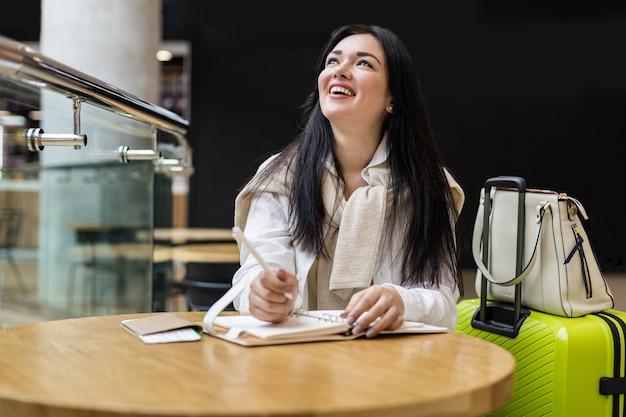 Femme souriante écrivant en prenant des notes dans le journal assis à table dans le terminal de l'aéroport international