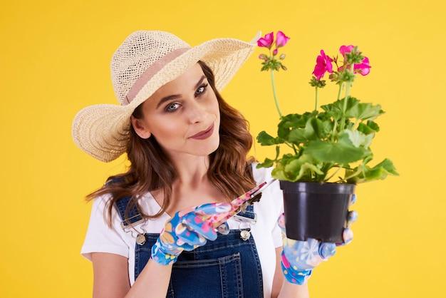 Femme souriante élagage fleur en pot de fleur