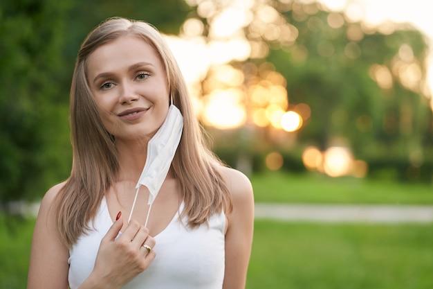Femme souriante enlevant le masque blanc