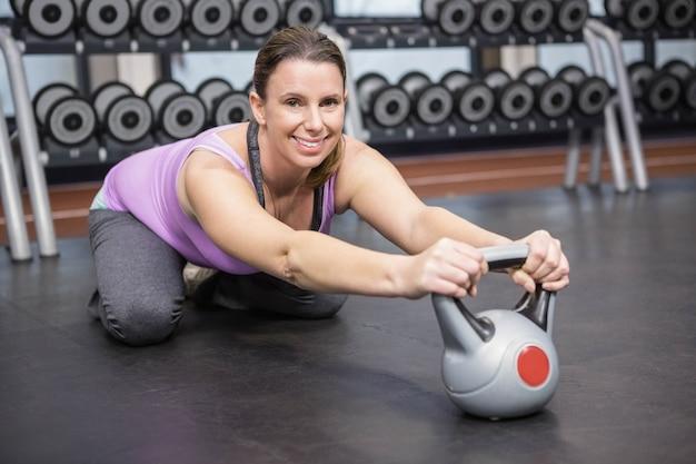 Femme souriante, entraînement avec kettlebell au gymnase