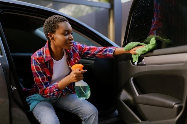 Une femme souriante essuie une voiture avec un chiffon, une station de lavage automatique des mains. industrie ou entreprise de lavage de voitures. la personne de sexe féminin nettoie son véhicule de la saleté à l'extérieur