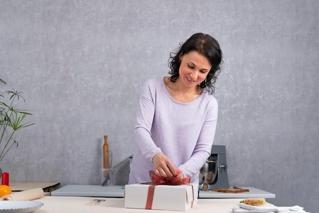 Femme souriante est un cadeau d'emballage dans une boîte en carton blanc avec ruban rouge. préparer les vacances.