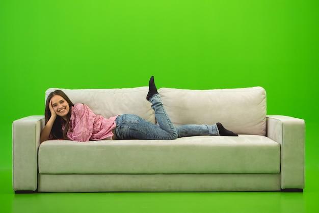 La femme souriante était allongée sur le canapé sur fond vert