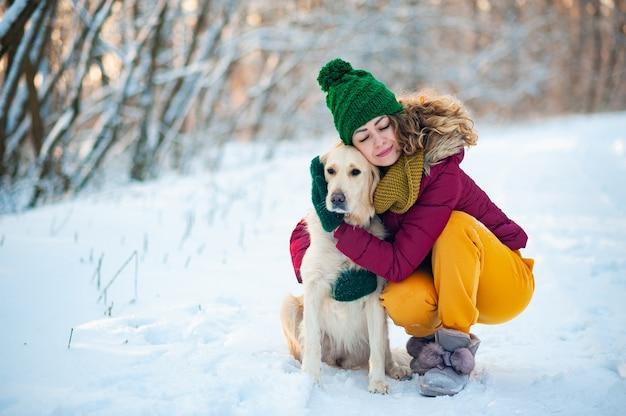 Femme souriante étreignant son chien de compagnie golden retriever