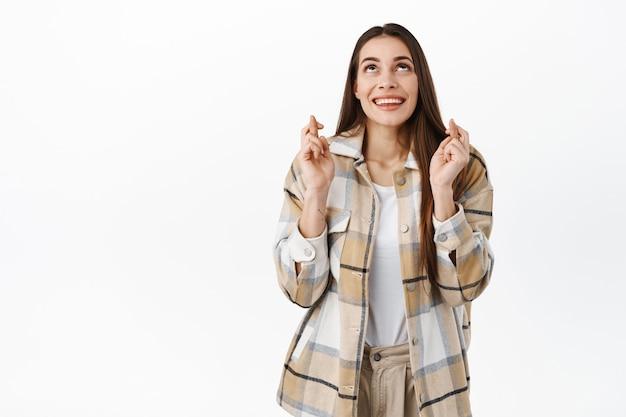 Une femme souriante et excitée lève les yeux et prie pour que le rêve se réalise, croise les doigts pour la bonne chance, regarde avec espoir au-dessus, debout contre un mur blanc