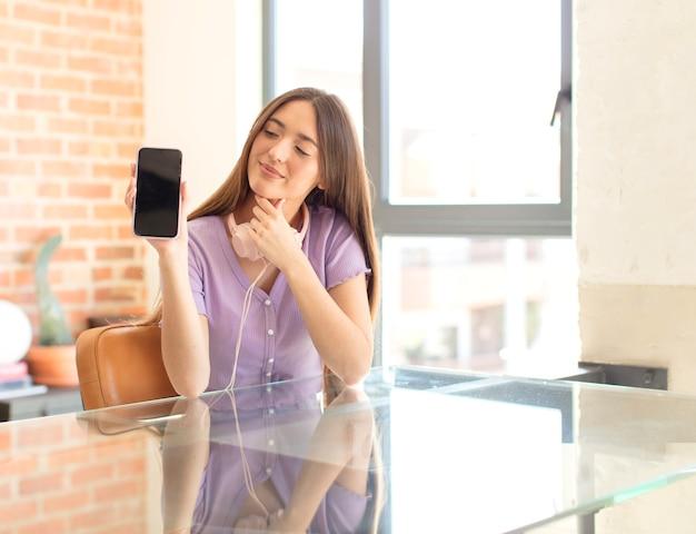 Femme souriante avec une expression heureuse et confiante avec la main sur le menton, se demandant et homme regardant sur le côté