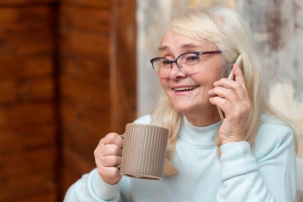 Femme souriante à faible angle parlant au téléphone