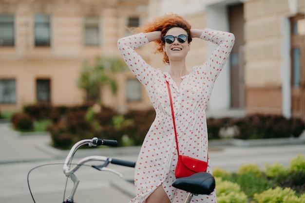 Femme souriante fait du vélo en ville, garde les mains derrière la tête