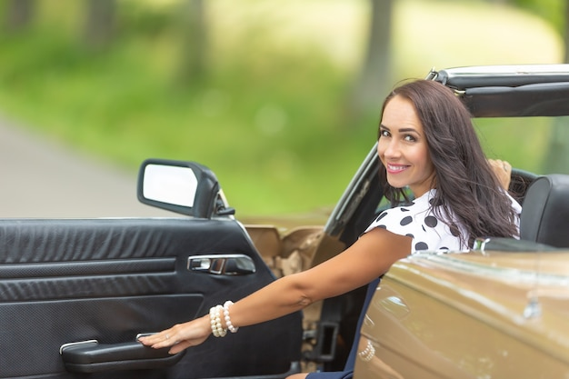 Femme souriante fermant la porte d'une voiture cabriolet regardant en arrière.