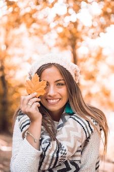 Femme souriante avec feuille d'automne