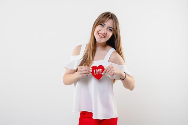 Femme souriante avec figure en forme de coeur avec mot d'amour isolé