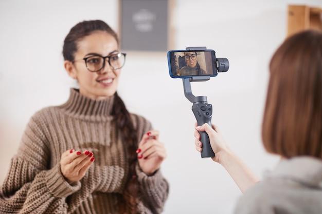 Femme souriante filmant une vidéo pour une chaîne de médias sociaux