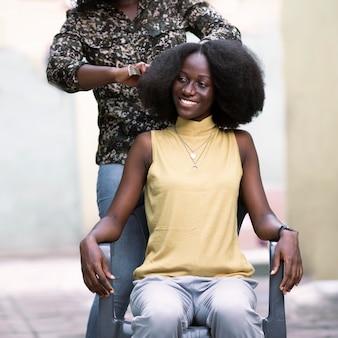 Femme souriante gros plan se brosser les cheveux