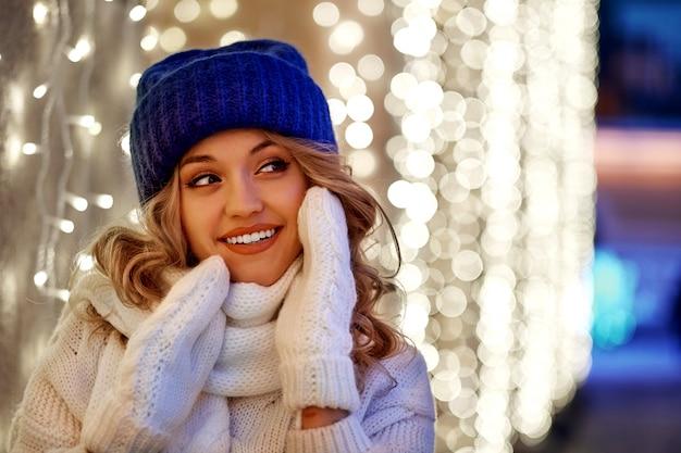 Femme souriante avec des guirlandes et des lumières de noël sur la fête de noël ou du nouvel an.