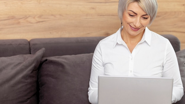 Femme souriante haute angle travaillant sur un ordinateur portable