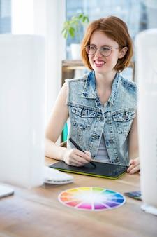 Femme souriante de hipster dessinant sur son bureau