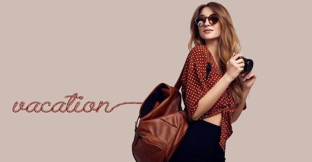 Femme souriante hipster étudiante avec sac à dos et appareil photo partant en vacances