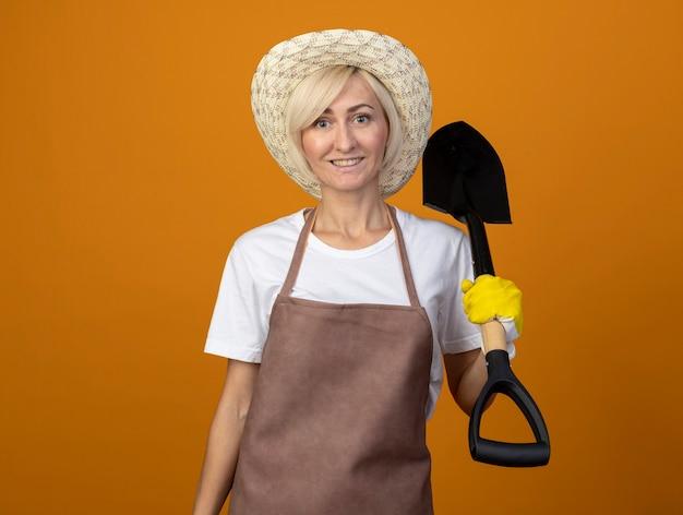 Femme souriante de jardinier d'âge moyen en uniforme de jardinier portant un chapeau et des gants de jardinage tenant une pelle regardant à l'avant isolée sur un mur orange avec espace de copie