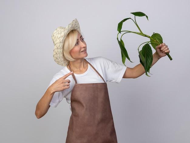 Femme souriante de jardinier blonde d'âge moyen en uniforme portant un chapeau tenant du doigt et regardant une plante isolée sur un mur blanc