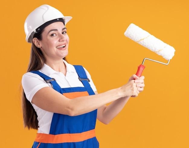 Femme souriante jeune constructeur en uniforme tenant une brosse à rouleau isolée sur un mur orange