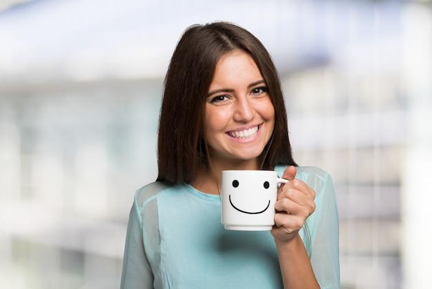 Femme souriante et joyeuse tenant une tasse souriante