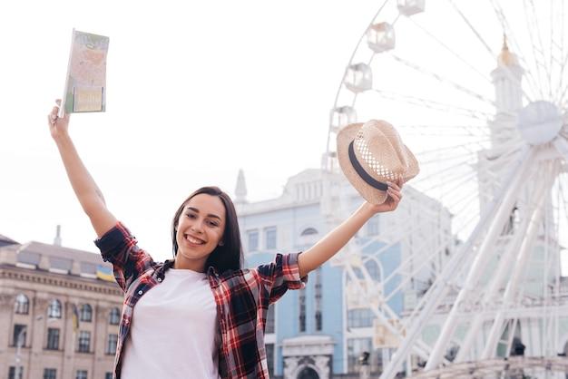 Femme souriante leva le bras avec carte et chapeau, debout près de la grande roue