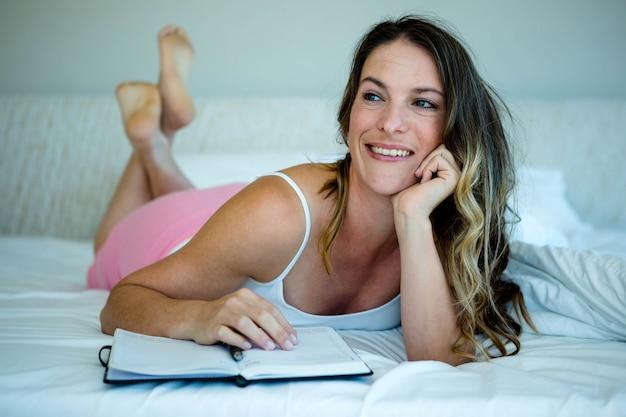 Femme souriante, lit, lit, livre