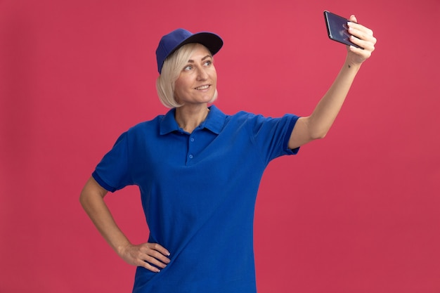 Femme souriante de livraison blonde d'âge moyen en uniforme bleu et casquette gardant la main sur la taille prenant un selfie isolé sur un mur rose