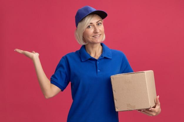 Femme souriante de livraison blonde d'âge moyen en uniforme bleu et casquette tenant une boîte en carton regardant à l'avant montrant une main vide isolée sur un mur rose