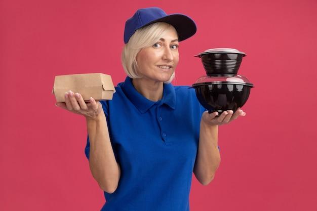 Femme souriante de livraison blonde d'âge moyen en uniforme bleu et casquette tenant un emballage de nourriture en papier et des contenants de nourriture regardant à l'avant isolé sur un mur rose