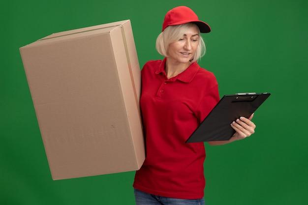 Femme souriante de livraison blonde d'âge moyen en uniforme rouge et casquette tenant une boîte en carton et un presse-papiers regardant le presse-papiers isolé sur un mur vert
