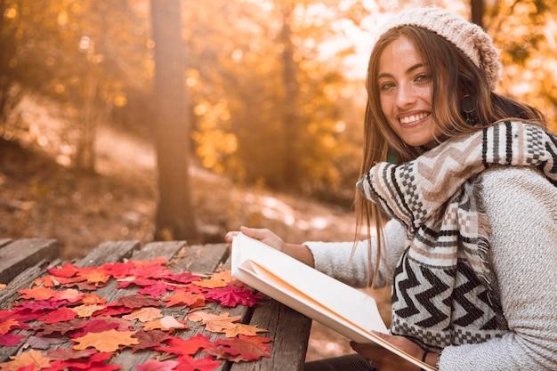 Femme souriante, à, livre, reposer, dans, automne, parc